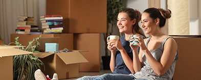 two women drinking coffee resting, moving boxes